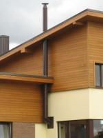 kaminas ant namo su medžio apdaila